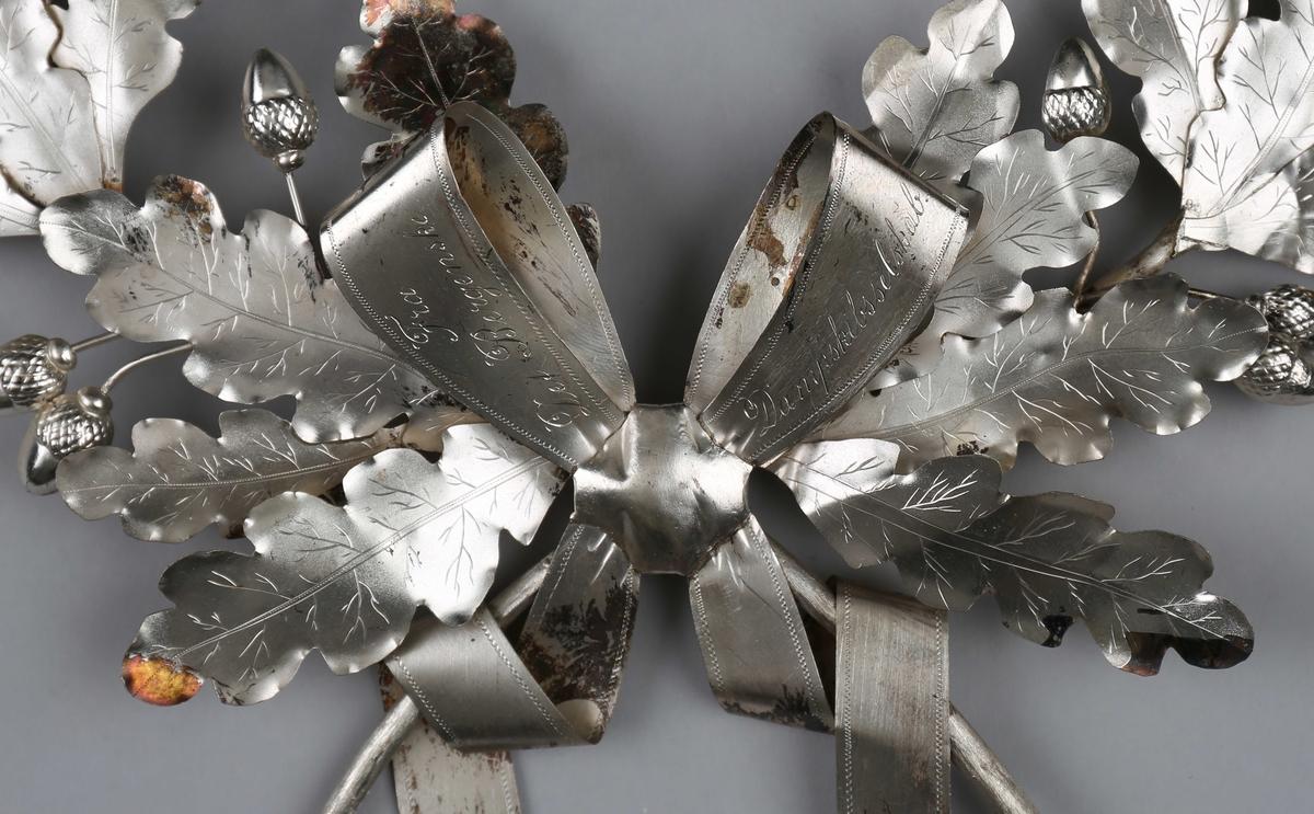 Bårekrans. Krans nedlagt på konsul Peder Jebsen´s båre 1892,  fra det Bergenske Dampskipsselskab. Kransen er utført som eikeblader med nøtter, samt sløyfe.