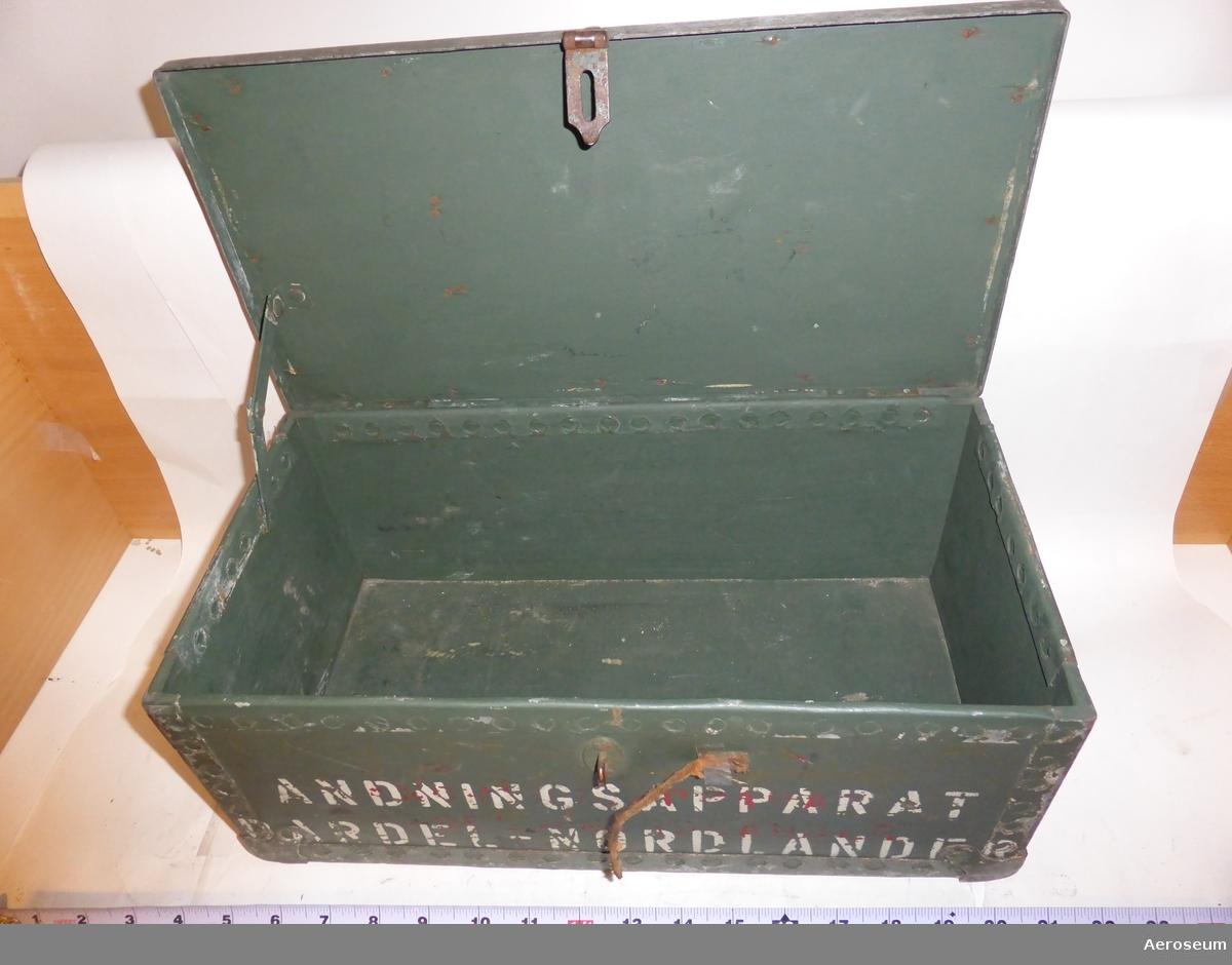 """En grön trälåda för andningsapparat. Dock är lådans ursprungliga innehåll försvunnet. På locket står det: """"5"""" och det finns ett läderhandtag och ett rött kors mot en vit cirkel. På framsidan står det: """"ANDNINGSAPPARAT DARDEL-NORDLANDER""""."""