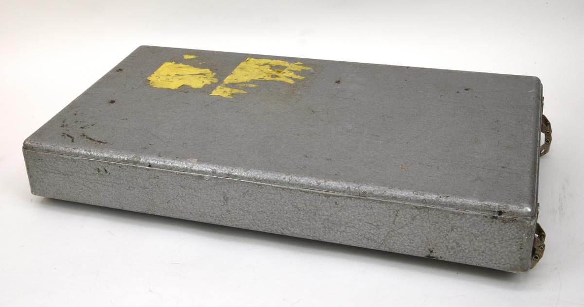 """Felten & Guilleaume Kopplungmesser für Kapazitive Kopplungen KKM-2. Mätinstrument som använts för att mäta och eliminera kapacitiv koppling (:1). Höljet av plåt är målat med grå hammarlack. Det är rektangulärt och har rundade kanter och hörn samt ett avtagbart lock av plåt som fästs med fyra spännen (:2). Manöverpanelen är av eloxerad aluminiumplåt som även är målad i en grågrön nyans med text på tyska och engelska tryckt i svart. På panelens nederkant finns en blå rand med tillverkarlogotyp, modellnamn och artikelnummer tryckt i svart. I det övre vänstra hörnet finns en separat panel med banankontakter för extern strömförsörjning och strömbrytare och under panelen finns plats för nio batterier av R20-typ.  För inställningar och justeringar finns en mängd reglage i form av vred och skjutreglar. Vreden har rattar i olika storlek av svart plast med olika färg på topparna för att indikera funktionen. På den vänstra delen av panelen finns sju gröna rattar i olika storlek, tre mindre rattar med grå topp, en röd ratt och tre skjutreglar. Där finns också en rektangulär amperemätare med vit mätartavla och grå ram tillverkad av Gossen. Den största gröna ratten """"Feinabgleich"""" och den lite mindre ratten """"Grobabgleich"""" har ett gemensamt fönster där vita skalskivor med svart och röd text syns. Även ratten """"Meßart"""" har ett skalfönster.  På den högra delen av panelen finns två rader med sex röda rattar vardera följt av två avlånga multipinkontakter i svart plast och en rad med elva banankontakter med bruna och svarta höljen samt en med gult hölje. Ovanför raderna med röda rattar finns en avtagbar kondensator i bakelit som sitter i banankontakter.  På höljets undersida finns två trämedar och på kortsidorna finns utfällbara metallhandtag. Bakom handtagen finns spår av någon form av märkning i tusch som nötts bort, endast """"Cst"""" är läsligt (dvs Stockholm C). På locket finns spår av gula etiketter, möjligen adresslappar. På den högra kortsidan finns en plakett med tillverkarnamn, model"""