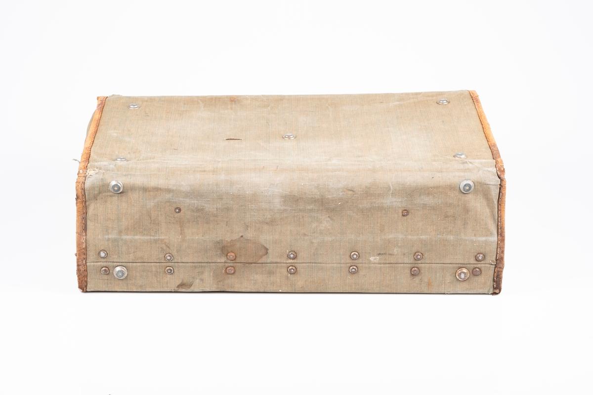 Reisekoffert med grønn trekk og lærkanter. Metallknotter på alle sider. Den har en typisk koffertlås med nøkkelhull, mangler nøkkel. Håndtaker er av lær. På innsiden er det lærremmer, den høyre lærremmen har spenne. Kofferten er fôret med grålilla stoff. Det er påført tekst på framsiden og venstre side.