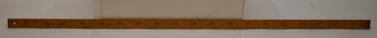 """En trälinjal på 100 centimeter försedd med mässingsbeslag i båda ändar.  Linjalen är på framsidan märkt med """"S.J."""" samt """"P67"""" som också pryds med en krona. På baksidan är """"Brastad"""" skrivet för hand med en tuschpenna, denna text är nött och lite svår att urskilja. På baksidan är det med en kulspetspenna också skrivet """"90 x 35 x 55"""". I ena änden av linjalen finns  ett hål för att kunna fästa ett snöre vid den eller för att kunna hänga upp den på en spik på väggen, till exempel."""