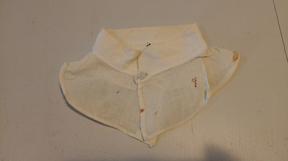 Oppstående linning av dobbelt hvitt bomullslerret, med avrundete hjørner og 1 håndsydd knapphull påhver side foran. På den ene sida også en liten knapp. Linningen er sydd til et stykke av tynnere hvitt bomullslerret. Det er brukt 1-tråds symaskin.