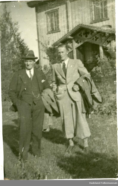 Petter Sinnerud og Hans Engnestangen stående utenfor et hus med utskjæringer i inngangspartiet.