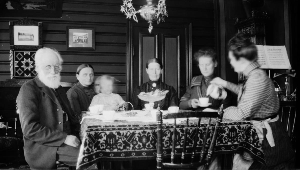 Fem voksne og ett barn rundt kaffebordet, antakelig på Linjordet i Østre Gausdal
