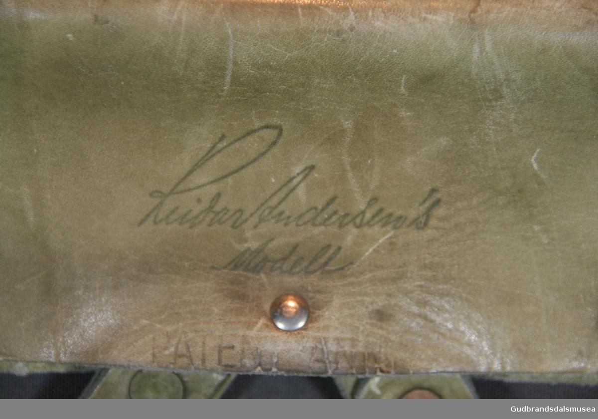 """Ryggsekk fra 1950-tallet, """"Rondane, Reidar Andersen's modell"""". Grått lerretssstoff, meis av jern. To lommer på siden, en lomme på front og topplokk lukkes med lærreimer og metallspenner. Reimer sydd på sekken. Ekstralomme på lokk, innside lukkes med glidelås i metall. Lommer og lokk forsterket med påsydd lærkant. Hoderommet lukkes med snøring i metallmaljer. Ryggreimer av lær med skulderbeskyttere av vadmel. Korsryggstøtte i kraftig stoff, boltet til meisendene. Lærholder over og rundt meisender i toppen, fastsydd til sekken."""