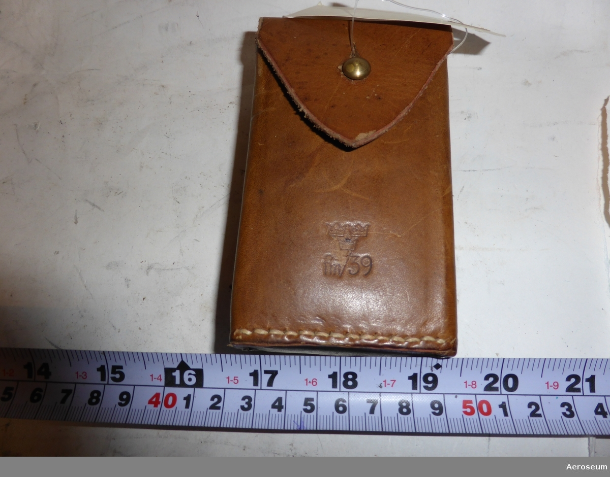 """En kompass i läderfodral. Tillverkad av Silva, typ 15. Är i gott skick i ett använt fodral. Fodralet stämplat invändigt med: """"BESIKTIGAT och GODKÄNT KAFI 22"""". Utvändigt präglat med symbolen för tre kronor och """"fm/39"""". Två små pappershäften i gott skick medföljer. Det ena är en slags bruksanvisning: """"med armékompassen i skog och mark SILVA"""". Det andra pappershäftet har två rubriker: """"Den NYA SILVA typ 15 T"""" och """"SILVA typ 15 TD"""". På själva kompassen står det: """"SILVA® TYP 15""""."""