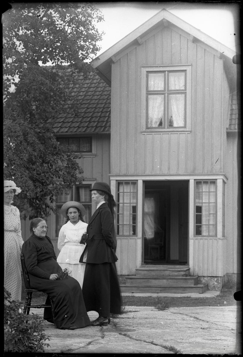 Kvinnor framför hus