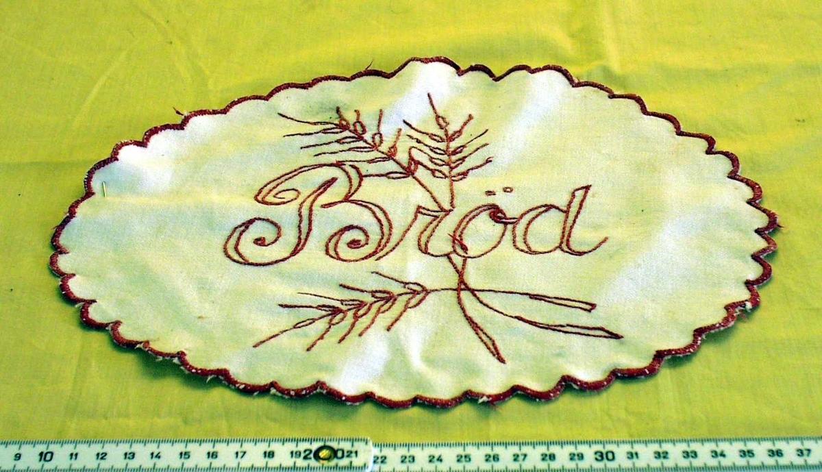 """Hvit duk. Brodert med rød tråd: Ordet """"Bröd"""", kornaks og bord rundt hele duken."""