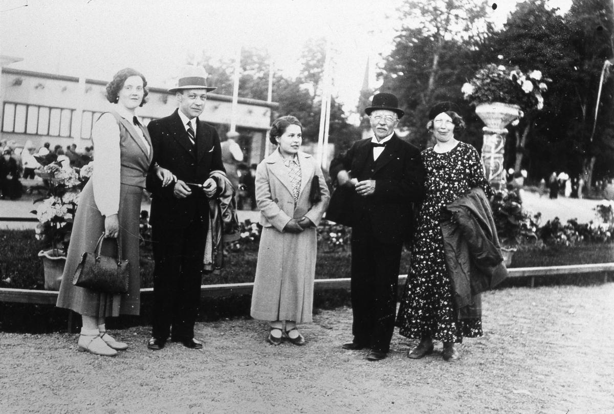 Den äldre mannen är tapetserarmästare Jansson. Han är vice ordförande i bestyrelsen för Arbogautställning. Han ska besöka utställningen tillsammans med sin familj. De står intill en blomsterplantering. Platsen är nuvarande Olof Ahllöfs park. Kägelbanan ligger utanför bild, till vänster.
