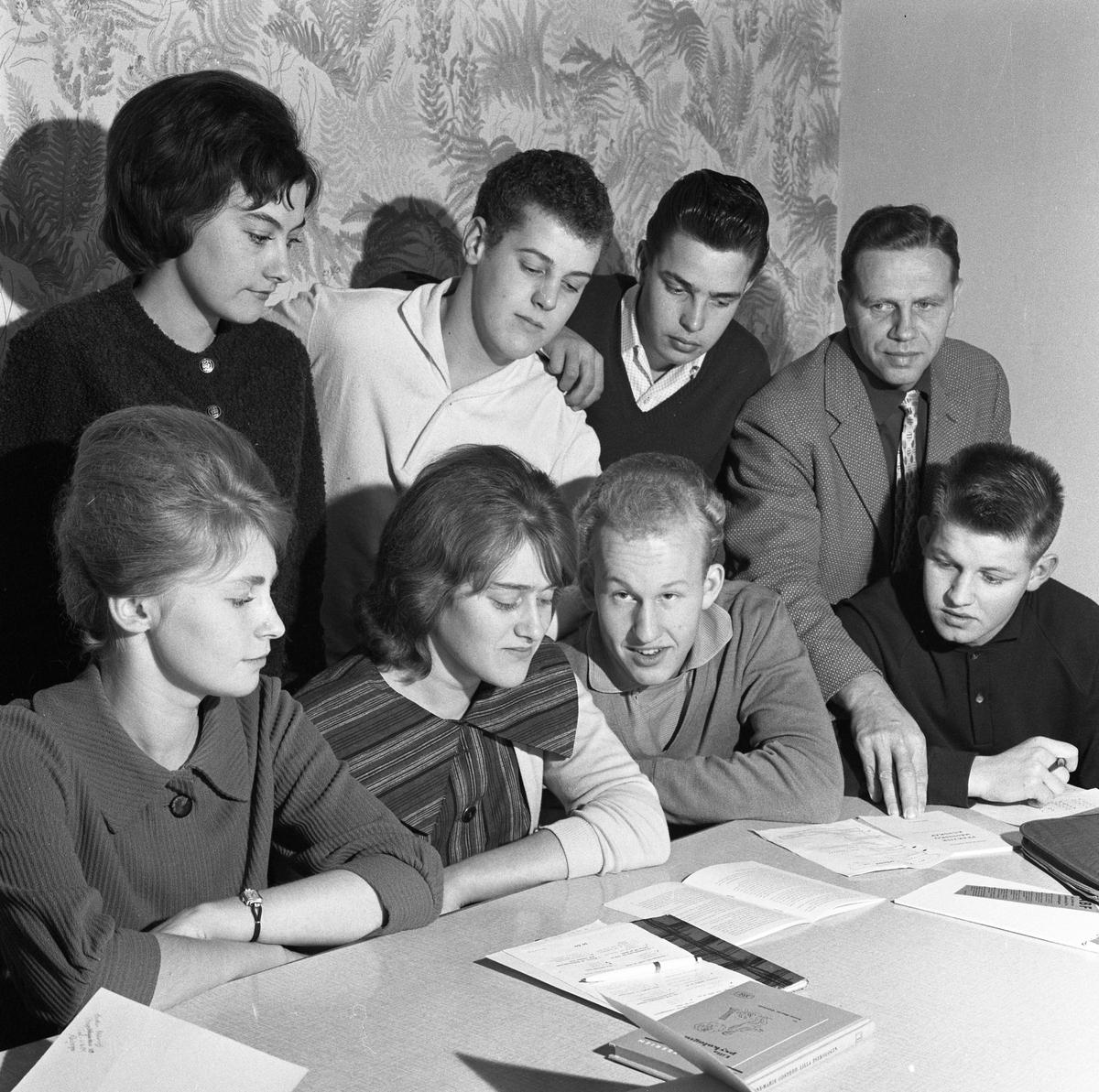 Arbetarnas Bildningsförbunds ungdomsskola En lärare och sju elever. Skrivhäften på bordet.