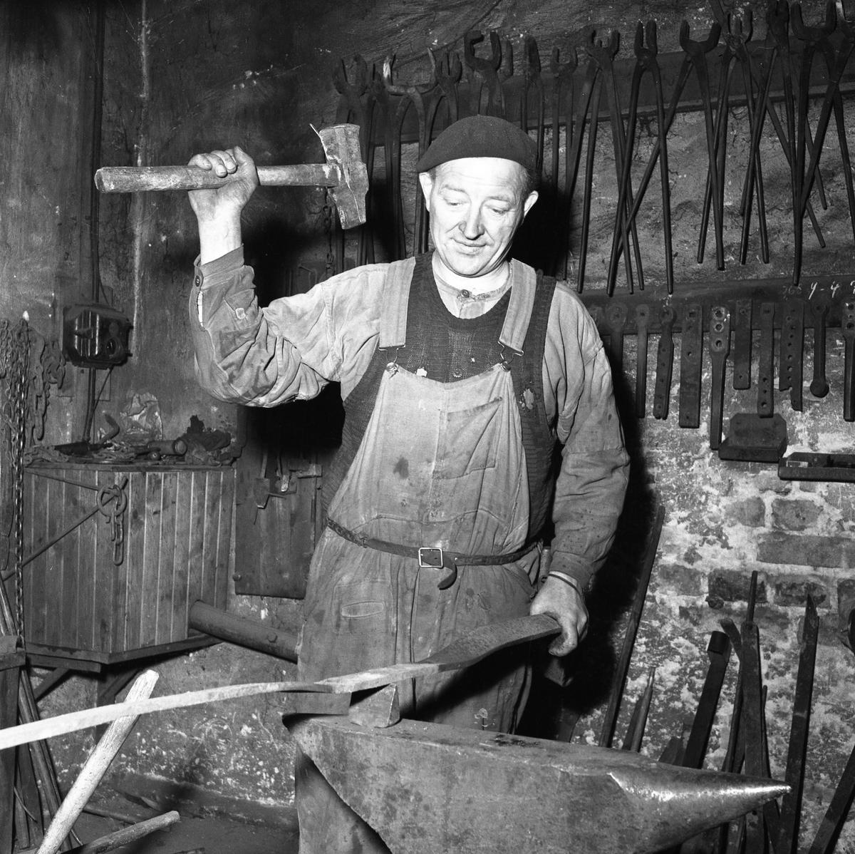 Albin Zander, smed på Jäders Bruk. Man klädd i basker och förkläde. Han håller ett verktyg i handen. På väggen hänger tänger och andra verktyg. Han befinner sig i smedjan. Bilden togs till en artikel i Arboga Tidning gällande kommunsammanläggningen.