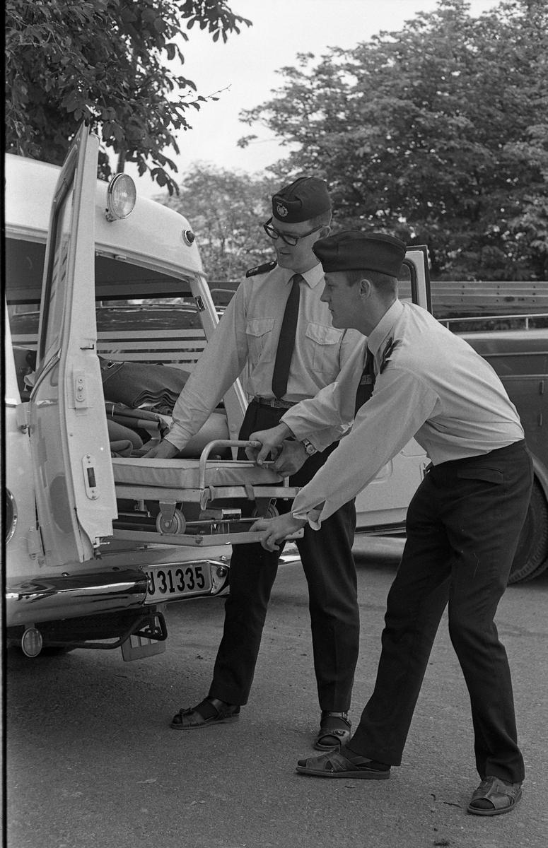 """Tage Andersson (till vänster) och Bengt """"Kos"""" Svensson (till höger) drar ut bårvagnen ur den nya ambulansen. Både Tage och Bengt är deltidsanställda på ambulansen. Den nya ambulansen ersätter den som krockade i olyckan på Annandag Pingst.  Två uniformsklädda män och en ambulans. Bilden är tagen på Strandvägen."""