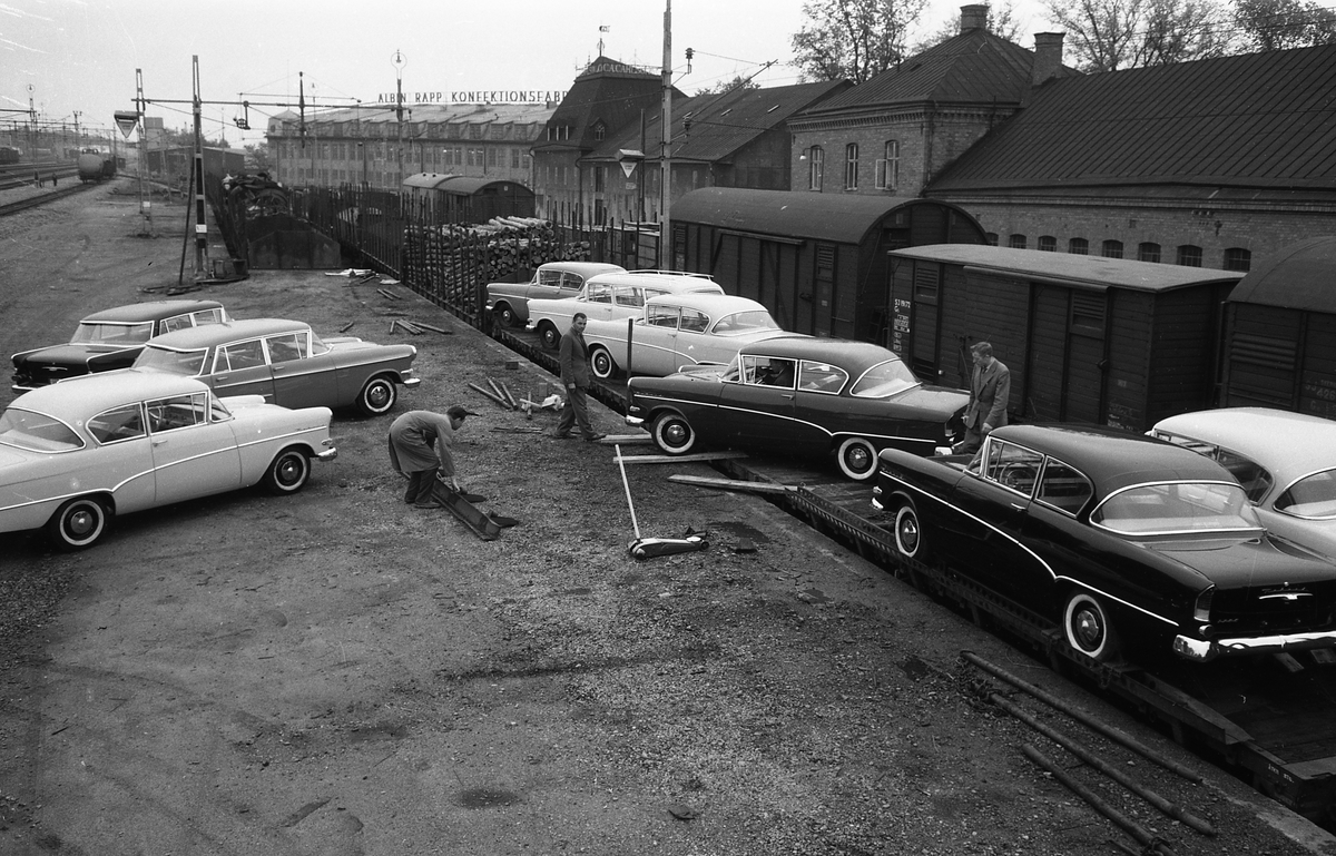 """Flera bilar, av märket Opel Kapitan, anländer med tåg. Här körs de av järnvägsvagnarna. Bilarna ska till Arboga Bil AB för försäljning.  I bakgrunden syns """"Rappshuset"""", Albin Rapp Konfektionsfabrik och järnvägsspår."""