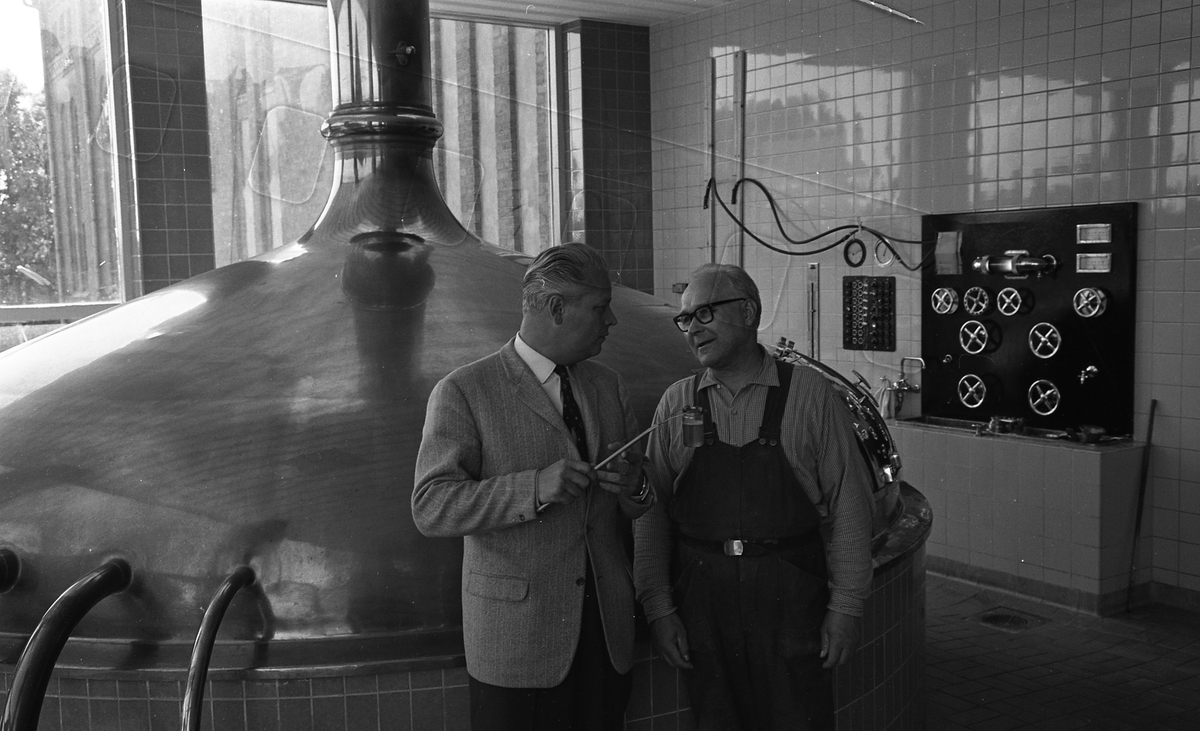 Arboga Bryggeri, interiör. Två män diskuterar,den ene i kostym och slips och den andre i arbetsbyxor. Det finns flera rattar och vred på den kaklade väggen. Bilden är tagen i brygghuset. Direktör Karl Ivar Levert (till vänster). Mannen till höger är inte identifierad.  Anläggningen var färdigbyggd 1899 och verksamheten startade 1 november samma år. 24 oktober 1980 tappades det sista ölet, på bryggeriet. Märket var Dart. Läs om Arboga Bryggeri i hembygdsföreningen Arboga Minnes årsbok 1981