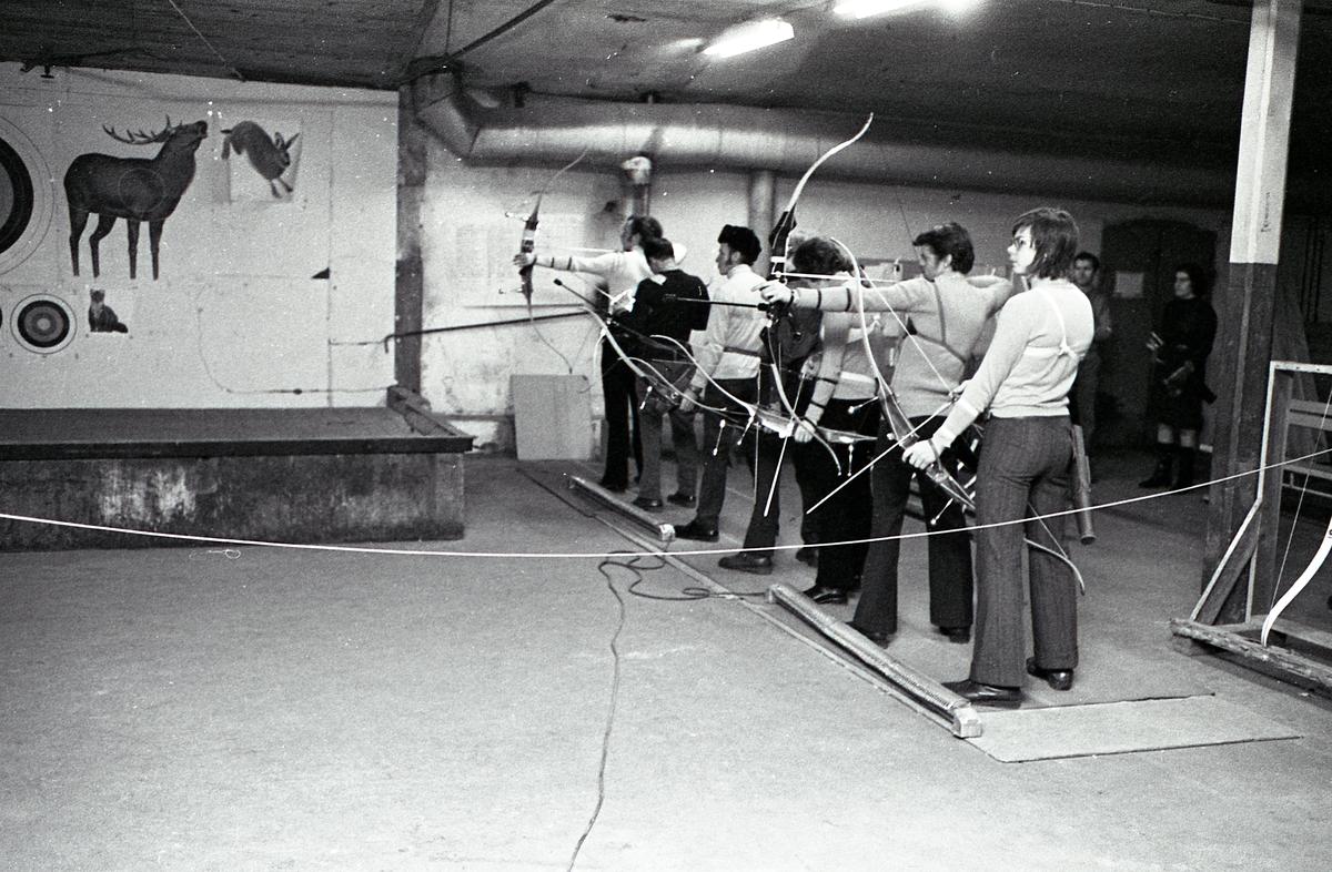 Inomhusträning hos Arboga Bågskytteklubb. Skyttarna står på rad, med pil och båge, och siktar på måltavlor som är till vänster utanför bilden. På väggen hänger viltdjursaffischer. Bakom skyttarna finns ställ för bågarna. Två personer står i bakgrunden och ser på.