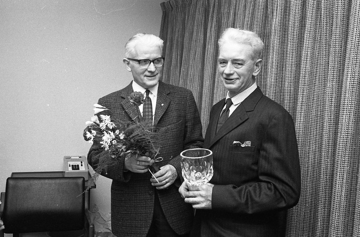 Pensionärsavtackning på Arboga Maskiner. Två män, iklädda kavaj och slips, står uppställda för fotografering. Den ene har en blomsterkvast och den andre håller i en glasskål. På ett bord, bakom dem, skymtar en räknemaskin. Namnuppgifter saknas.