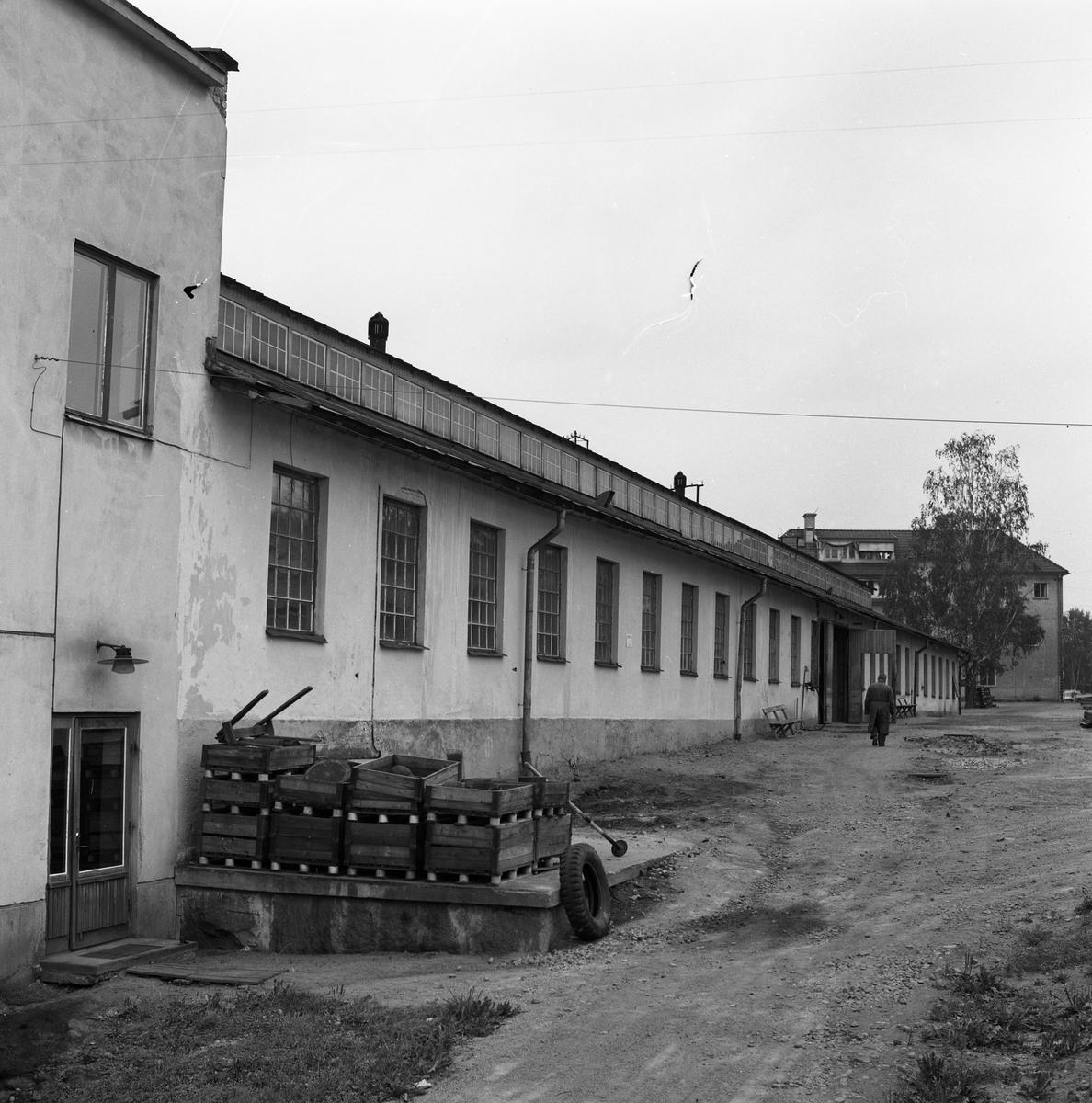 Exteriör av maskinverkstaden vid Meken, Arboga Mekaniska Verkstad på 1960-talet. Verkstaden är en lång byggnad. Till vänster ses en entré med glasdörr. Utanför dörren ligger trälådor staplade. En man går på vägen intill byggnaden.  25 september 1856 fick AB Arboga Mekaniska Verkstad rättigheter att anlägga järngjuteri och mekanisk verkstad. Verksamheten startade 1858. Meken var först i landet med att installera en elektrisk motor för drift av verktygsmaskiner vid en taktransmission (1887).  Gjuteriet lades ner 1967. Den mekaniska verkstaden lades ner på 1980-talet. Läs om Meken i Hembygdsföreningen Arboga Minnes årsbok från 1982.
