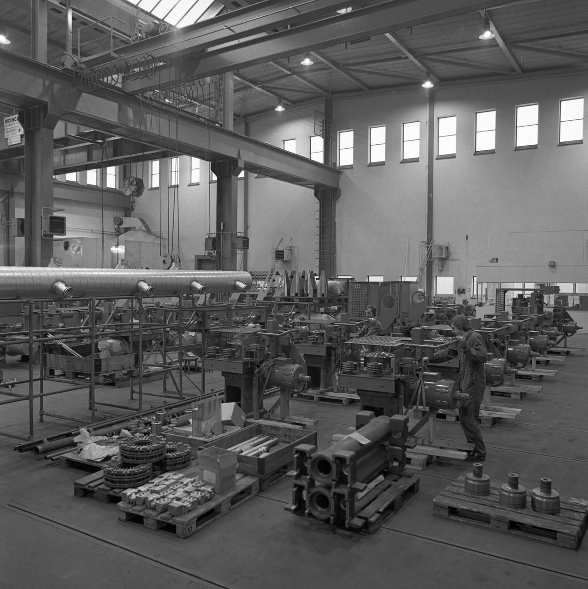 Arboga Mekaniska Verkstad, Meken, interiör från maskinverkstad och monteringsavdelning.  Industrilokal med högt i tak, traverser och maskiner i rader. Två män arbetar vid var sin maskin. 25 september 1856 fick AB Arboga Mekaniska Verkstad rättigheter att anlägga järngjuteri och mekanisk verkstad. Verksamheten startade 1858. Meken var först i landet med att installera en elektrisk motor för drift av verktygsmaskiner vid en taktransmission (1887).  Gjuteriet lades ner 1967. Den mekaniska verkstaden lades ner på 1980-talet. Läs om Meken i Hembygdsföreningen Arboga Minnes årsbok från 1982.