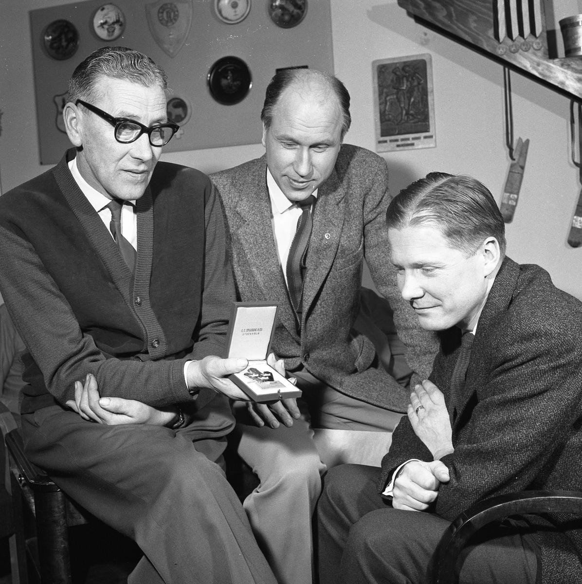 """Arboga Orienteringsklubb. Tre män tittar på en plakett som en av dem har i en ask. De befinner sig möjligen i en klubbstuga. Mannen i mitten är Lars Erjö. Från vänster: """"Pliggen"""" Lindén (har har en skoaffär), Lars Erjö (lärare) och okänd."""