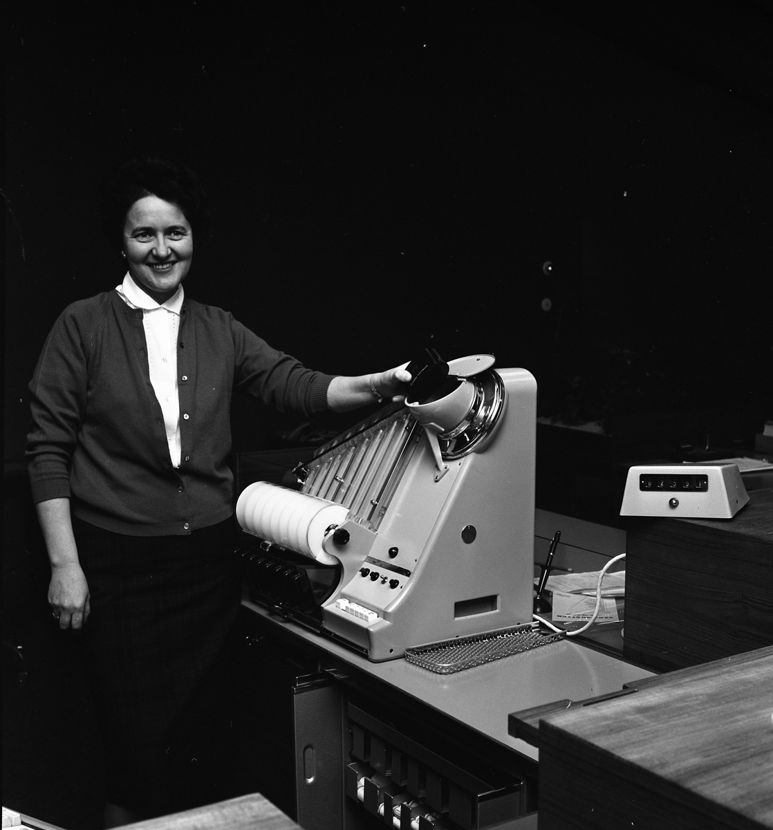 Arboga Sparbank, Margit Ander. En kvinna står vid en myntmaskin.