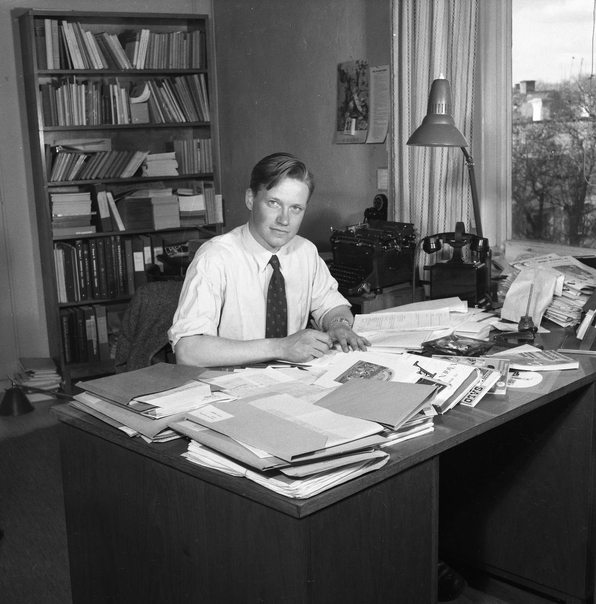 Arboga Tidning, personal och interiör. En man sitter vid ett skrivbord med en penna i handen. Möjligen är han journalist. Han har skjorta och slips på sig, kavajen har han hängt över stolsryggen. Skrivbordet är belamrat med papper och trycksaker. Där finns även en telefon, en askkopp och en skrivbordslampa. Skrivbordet står nära fönstret, det syns att mannens kontor ligger någon våning upp i huset. Vid sidan om honom, står ett litet bord med en skrivmaskin på. På väggen hänger en telefon (möjligen en interntelefon). Bakom sig har han en bokhylla full av böcker och pärmar. Det står till och med några böcker på golvet.