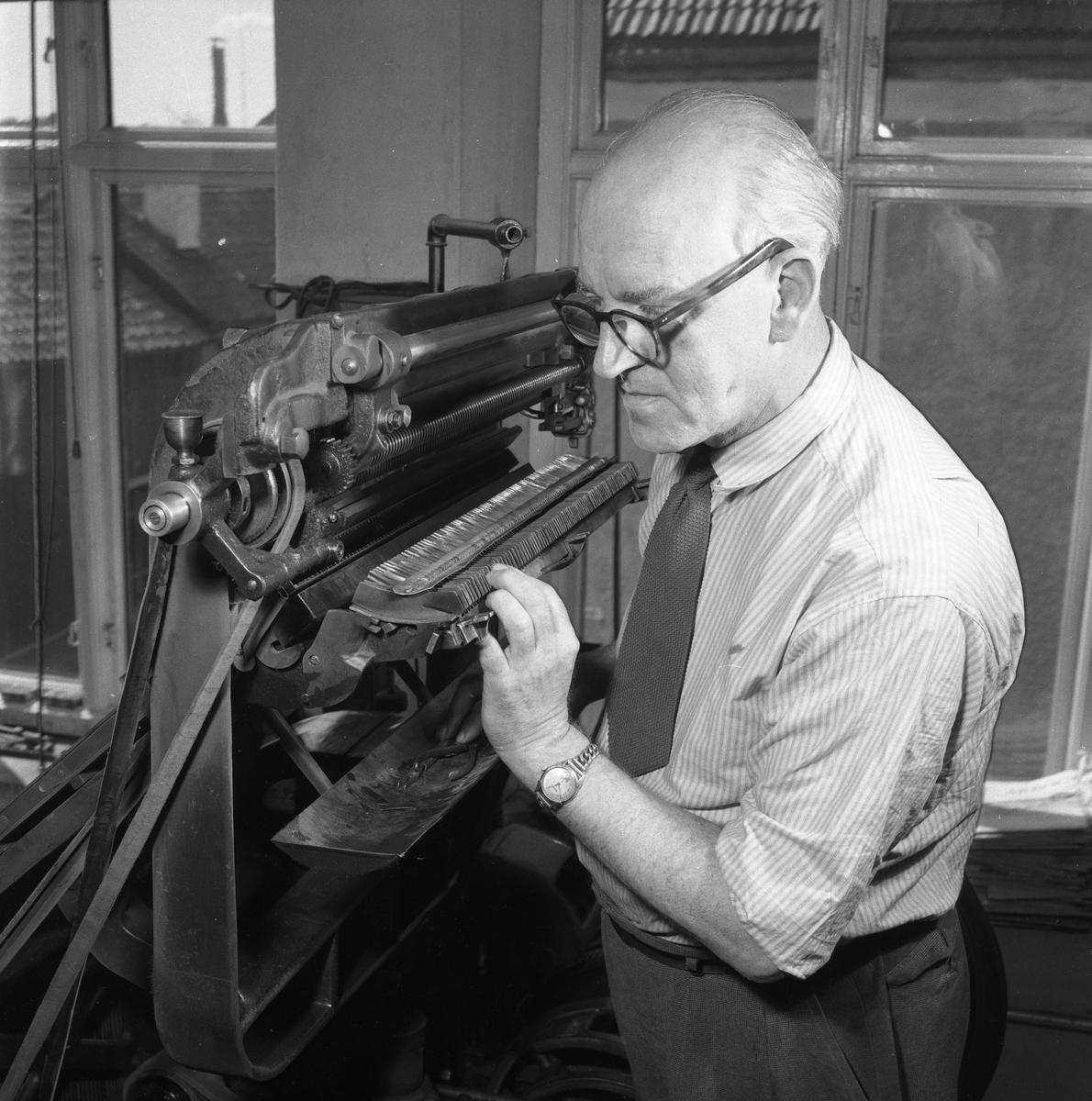 Arboga Tidning, personal och interiör. En man, iklädd skjorta och slips, arbetar vid en maskin. Utsikten genom fönstret visar, att lokalen ligger någon våning upp i huset.