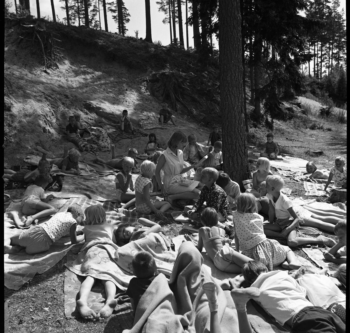 """Barnens Dagskolonin vid Högsjön, väster om Arboga. En """"fröken"""" har högläsning medan barnen ligger på filtar, i sluttningen, och hör på."""