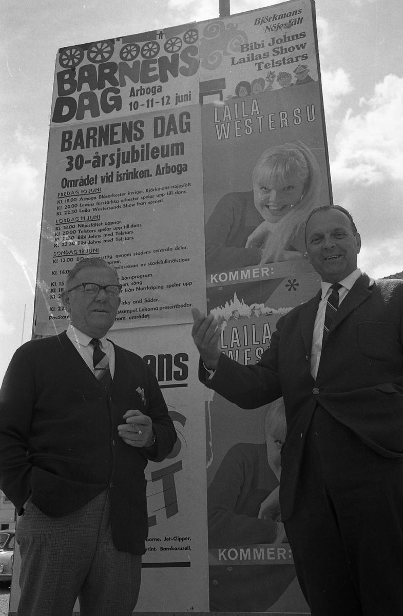 Barnens Dag firar 30-årsjubileum. Framför affischen med programpunkterna står Atschy Strandberg (till vänster) och Yngve Larsson (till höger).