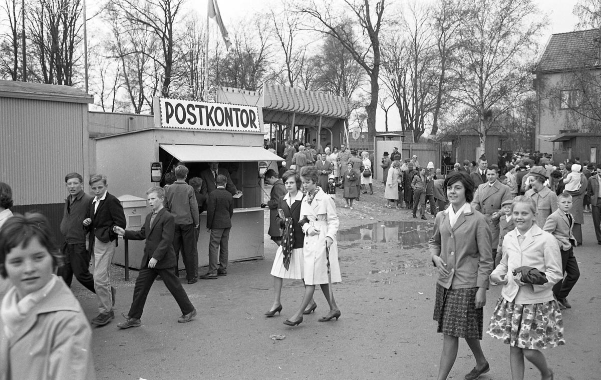 Barnens Dag firas. Ett tillfälligt postkontor har byggts upp. Besökarna är glada och finklädda trots att det har regnat. Här är en festplats med tivoli. Träden, i bakgrunden, står i Olof Ahllöfs park