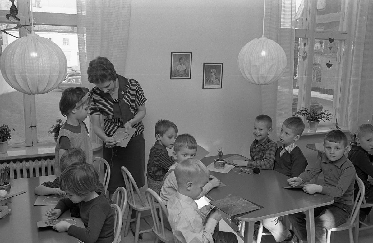 """Barnträdgård, Arbetarnas Bildningsförbund, ABF, på Stadsgården. Barnen sitter vid borden och syr snögubbar av garn på pappskivor. """"Fröken"""" hjälper till. Genom fönstret syns Stora torget."""