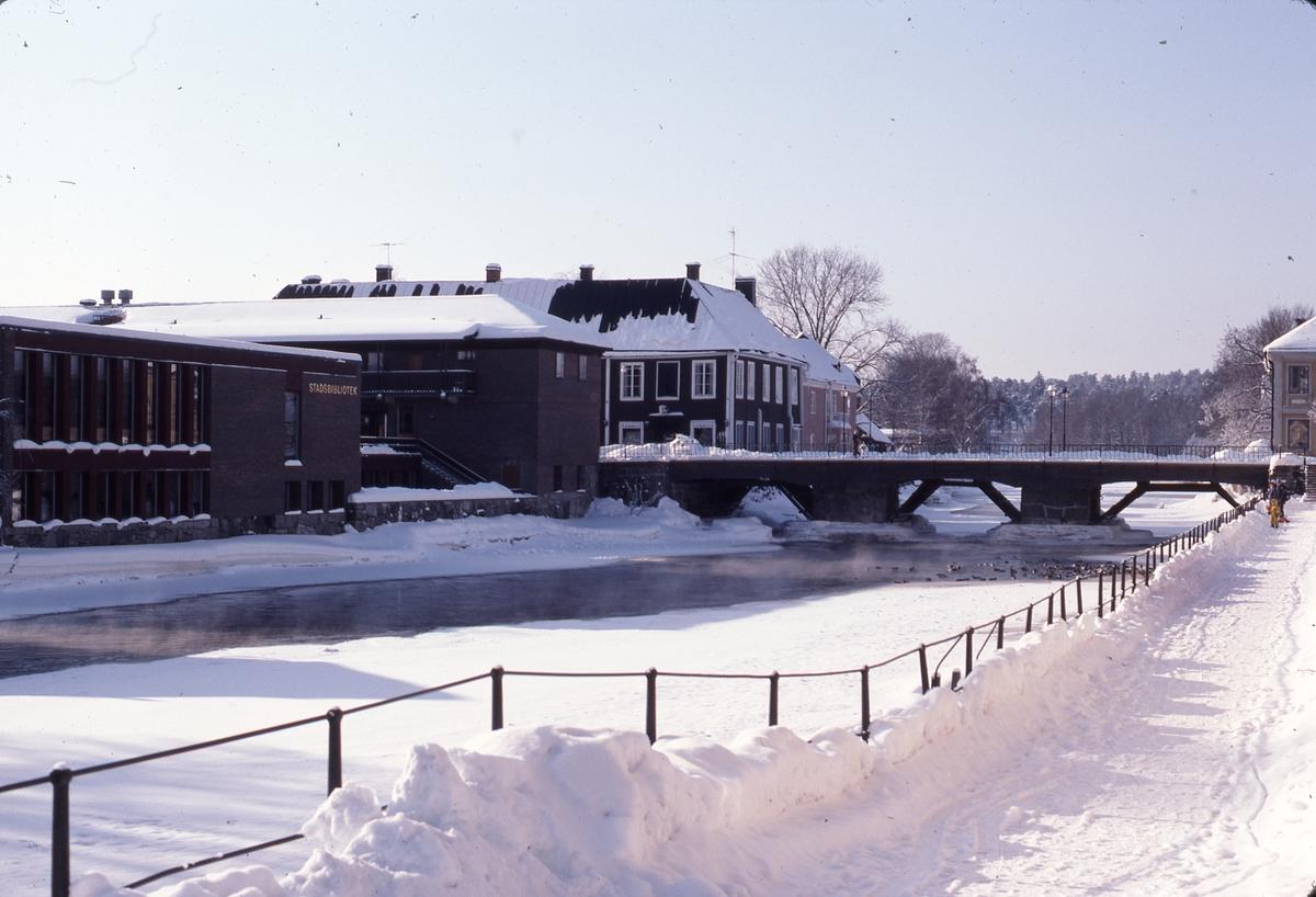 Biblioteket, Kapellbron och Labron/Ladbron i snö. Is och snö på Arbogaån. Två personer står nedanför trappan, från Kapellgatan, och matar änder i ån.