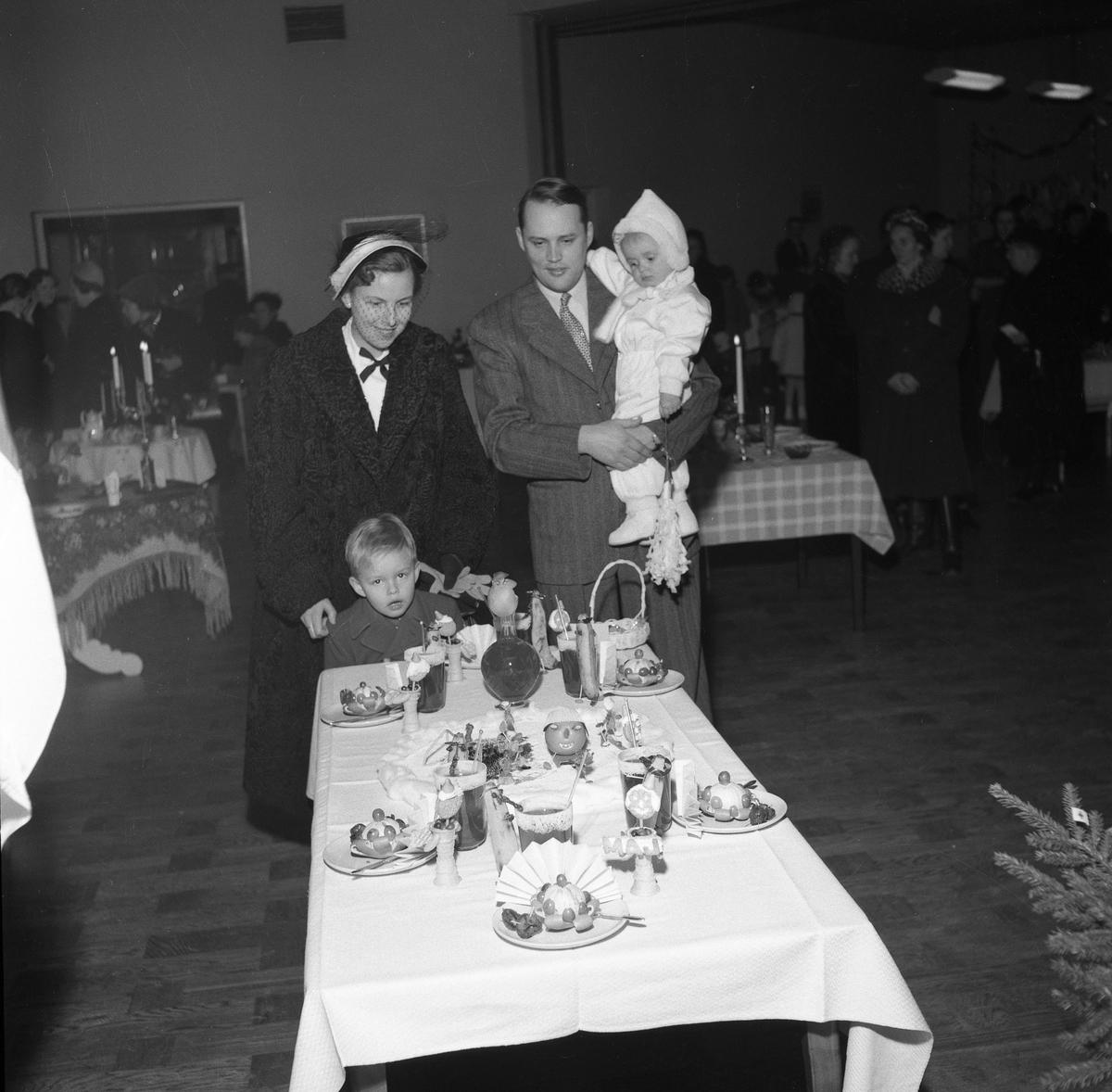 På Folkan/Medborgarhuset visas olika dukningar. En familj besöker utställningen och har stannat vid ett bord med dessert. Frukter som banan och apelsin ingår i efterrätten. Kanske är det glass på faten. Kvinnan bär päls och hatt med flor. Mannen har kostym. Han bär minstingen på armen. Storebror står vid mamma. Andra utställningsbesökare ses i bakgrunden.