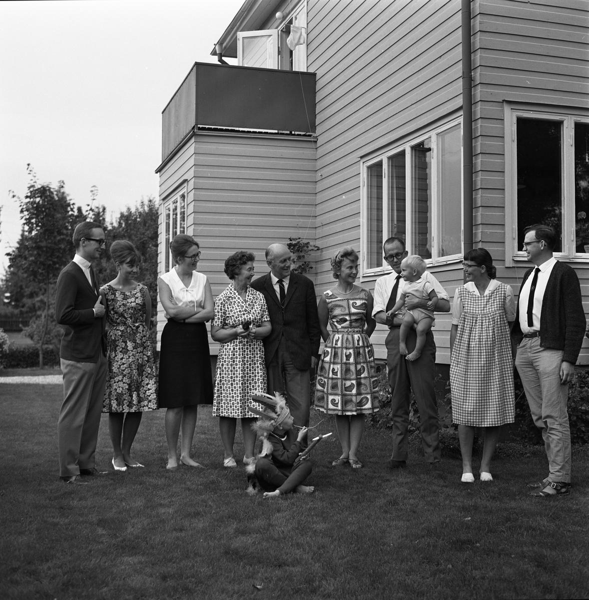 Bror och Karin Gustafsson med familj, samlade på gården vid Redskapsgatan. Längst till vänster står sonen Jan Brorsson.  Två små barn, varav den ene har indianskrud.