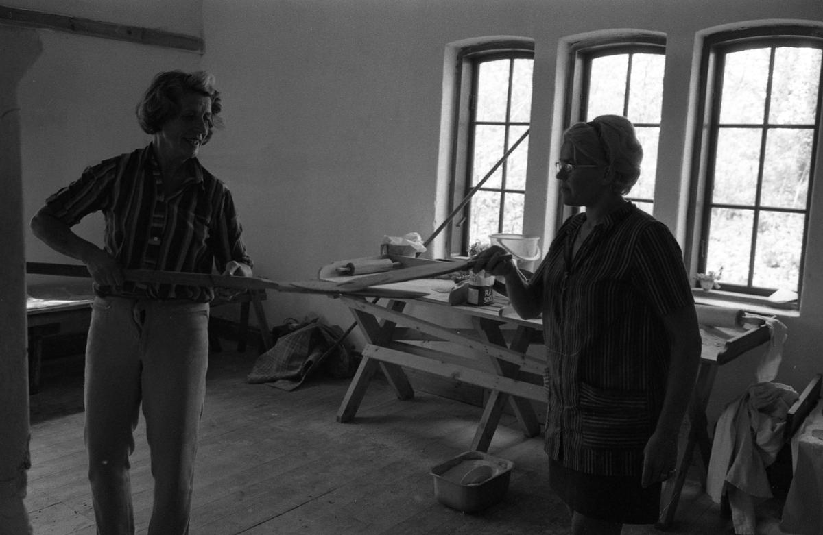Brödbakning vid Jäders bruk. Två kvinnor i en bakstuga/bagarbod. En kvinna håller i en brödspade. Möjligen bakar de knäckebröd. Vid det ena fönstret finns ett bakbord med brödkavel, mjölpåse, bunke och brödkavel.