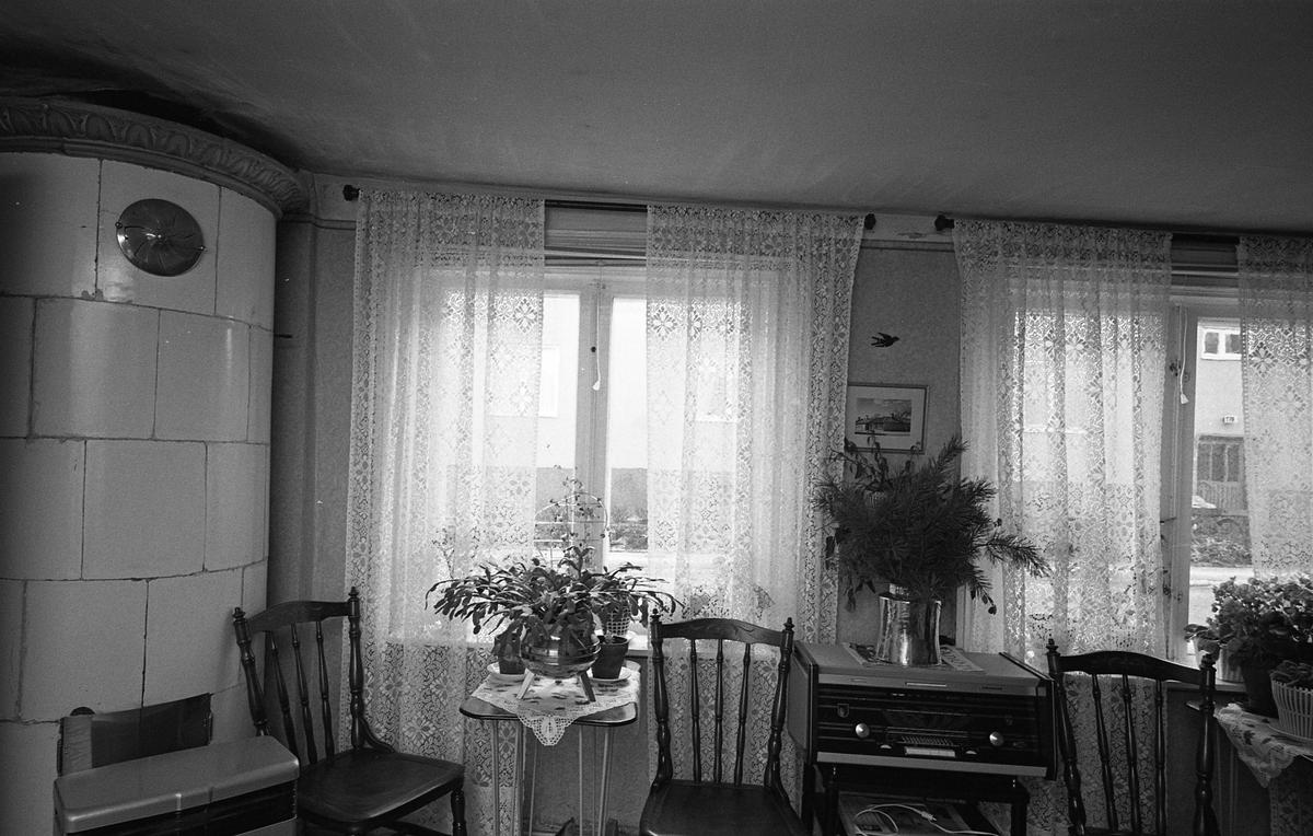 Interiör från bostad i kvarteret Tullnären, mellan Storgatan - Trädgårdsgatan och Herrgårdsgatan - Paradisgränd. I hörnet står en kakelugn. Framför fönstren står bord med krukväxter. Mellan de båda fönstren ses en radioapparat. Ovanpå den står en kruka (av koppar?) med tallris. Tre pinnstolar. Fotografens anteckning: Dokumentation av fastigheter i kvarteren söder och norr om ån. Bilder och beskrivning finns på Arboga Museum.