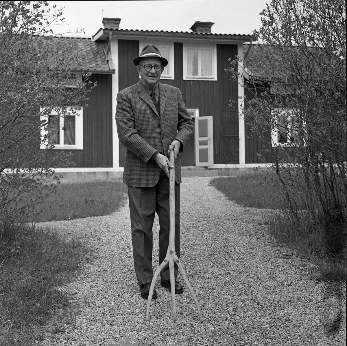 Doktor Bernhard Garsten, Medåker. På grusgången framför sitt hus. Han är klädd i hatt och kavaj. Han håller i en annorlunda grep.
