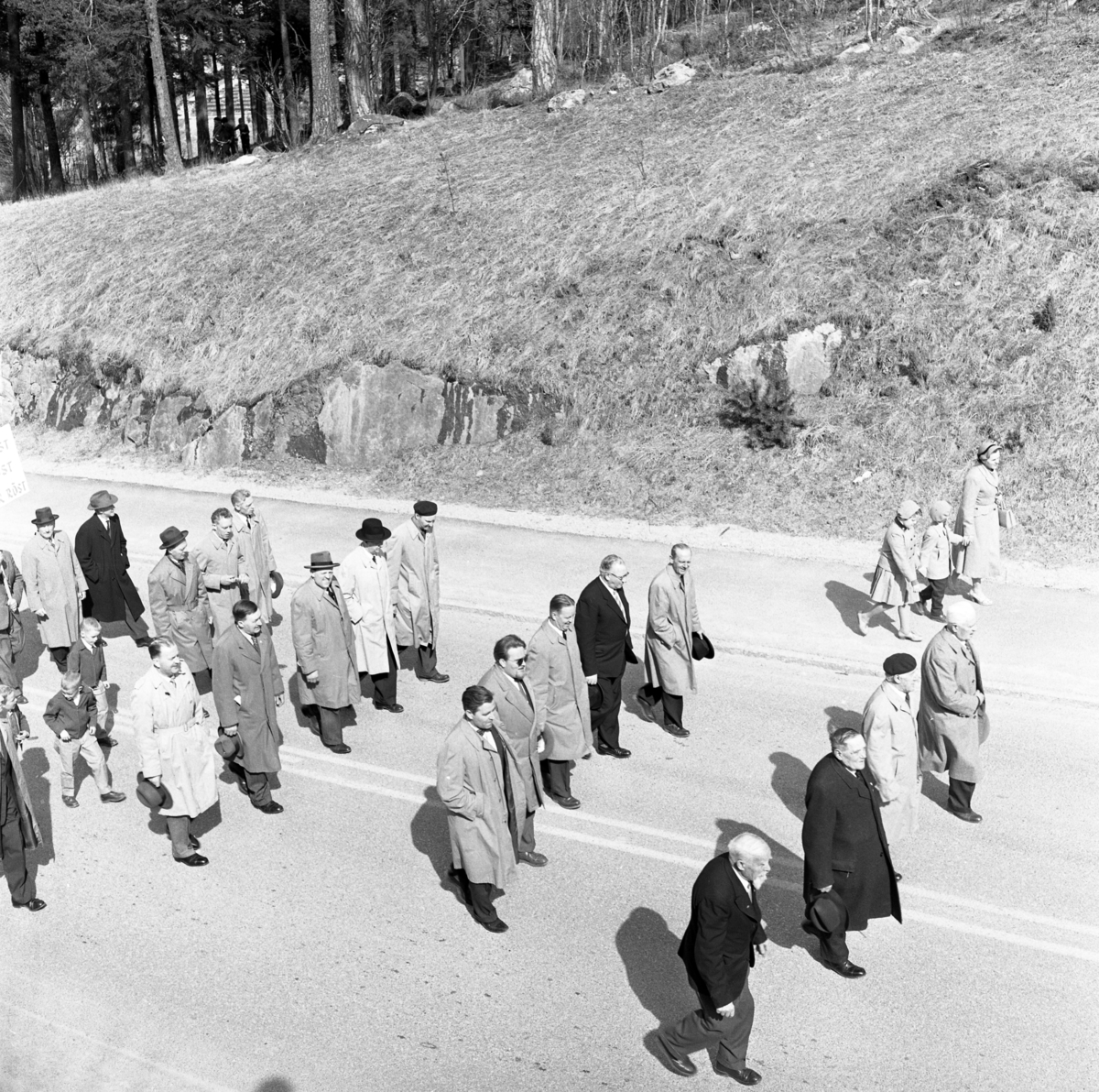 Första maj. Demonstrationståg. Herrar i hatt och överrock går i prydliga rader. Andra raden, närmast kameran, är Nils Brodin. En kvinna med två barn går utanför ledet.
