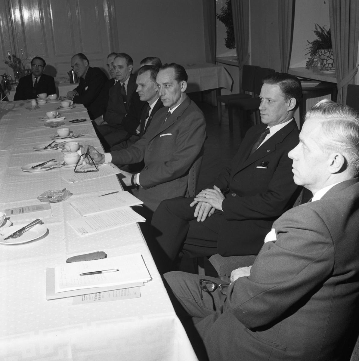 Hantverksföreningens PR-kurs Kostymklädda män sitter vid ett bord som är dukat med kaffekoppar och askfat.