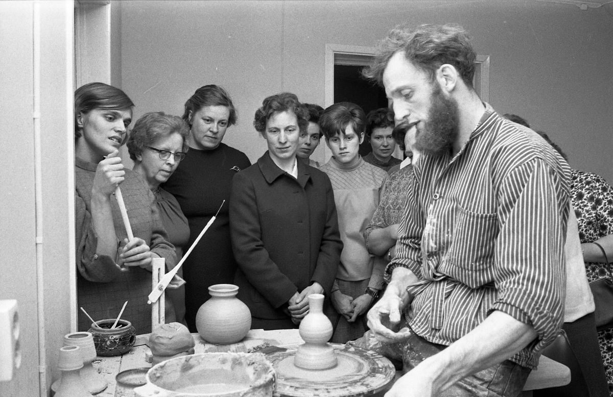 """Kerstin Hörnlund (längst till vänster) och Gösta Gräs har besök, i keramikverkstaden, av en grupp kvinnor. Gösta demonstrerar hur man drejar. Publiken tittar intresserat på. På ovanvåningen, i Åhuset, har paret sitt galleri. Läs Kerstins text """"Konstnärsliv i Arboga - möten och minnesbilder"""" i Arboga Minnes årsbok 1998."""