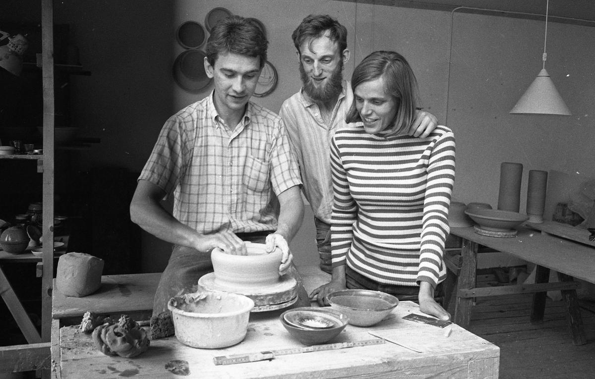 """Keramiker i arbete. Ulf Johansson drejar medan Gösta Gräs och Kerstin Hörnlund ser på. I lokalen ses arbetsbord och hyllor med keramik. Läs Kerstins text """"Konstnärsliv i Arboga - möten och minnesbilder"""" i Arboga Minnes årsbok 1998."""