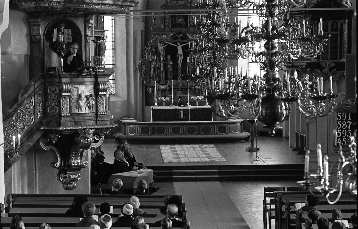 Heliga Trefaldighets kyrka, interiör. I predikstolen står pastor Eriksson från Missionskyrkan. Församlingsbor i kyrkbänkarna. I bilden ses ljuskrona, psalmtavla och altare, altartavla och dopfunt i koret.
