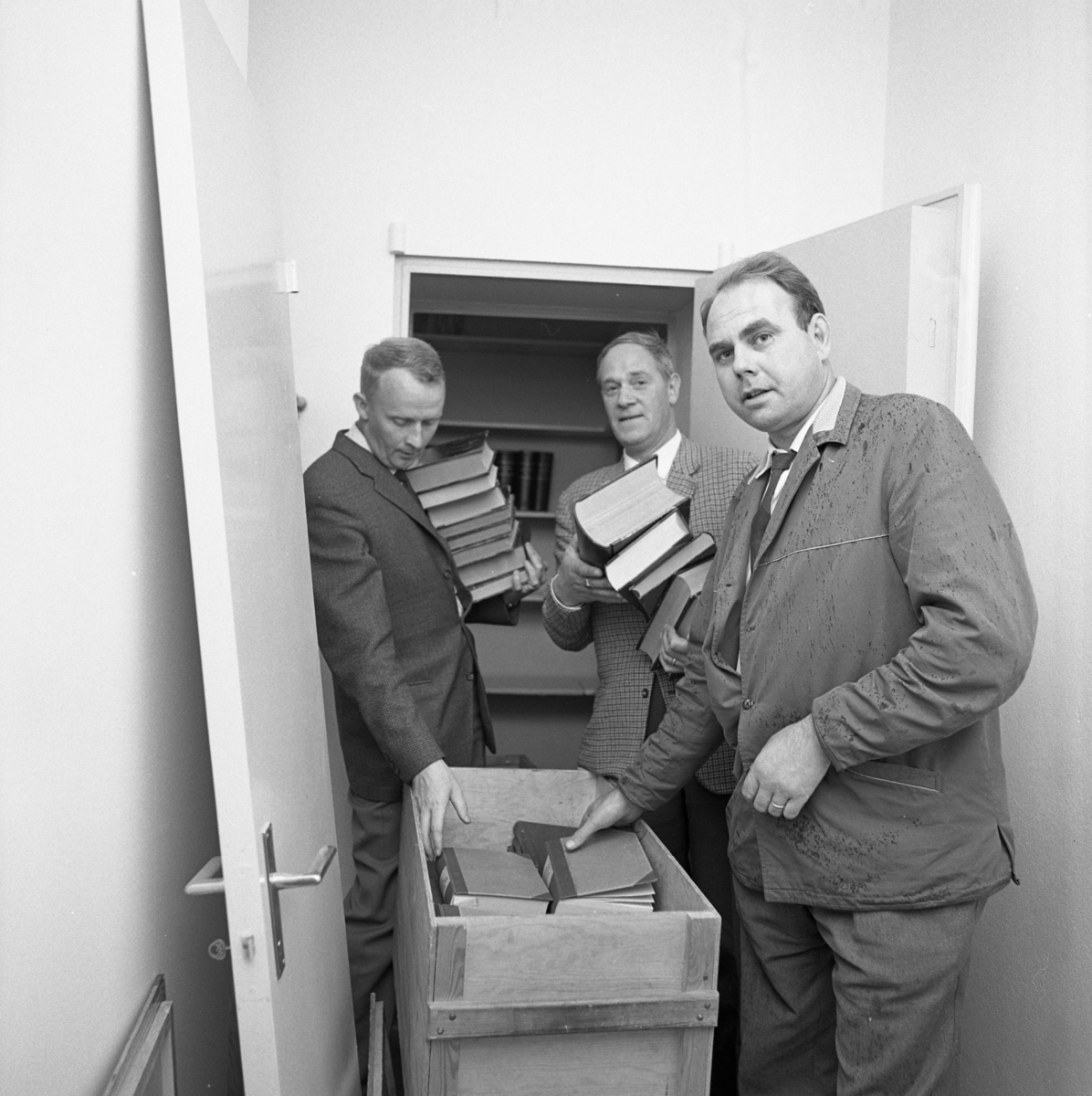 Polisen packar och flyttar från Rådhuset. Från vänster: Stig Söderling, Sigurd Granberg och Harry Hellenberg. Tre män packar tjocka böcker i en flyttlåda.