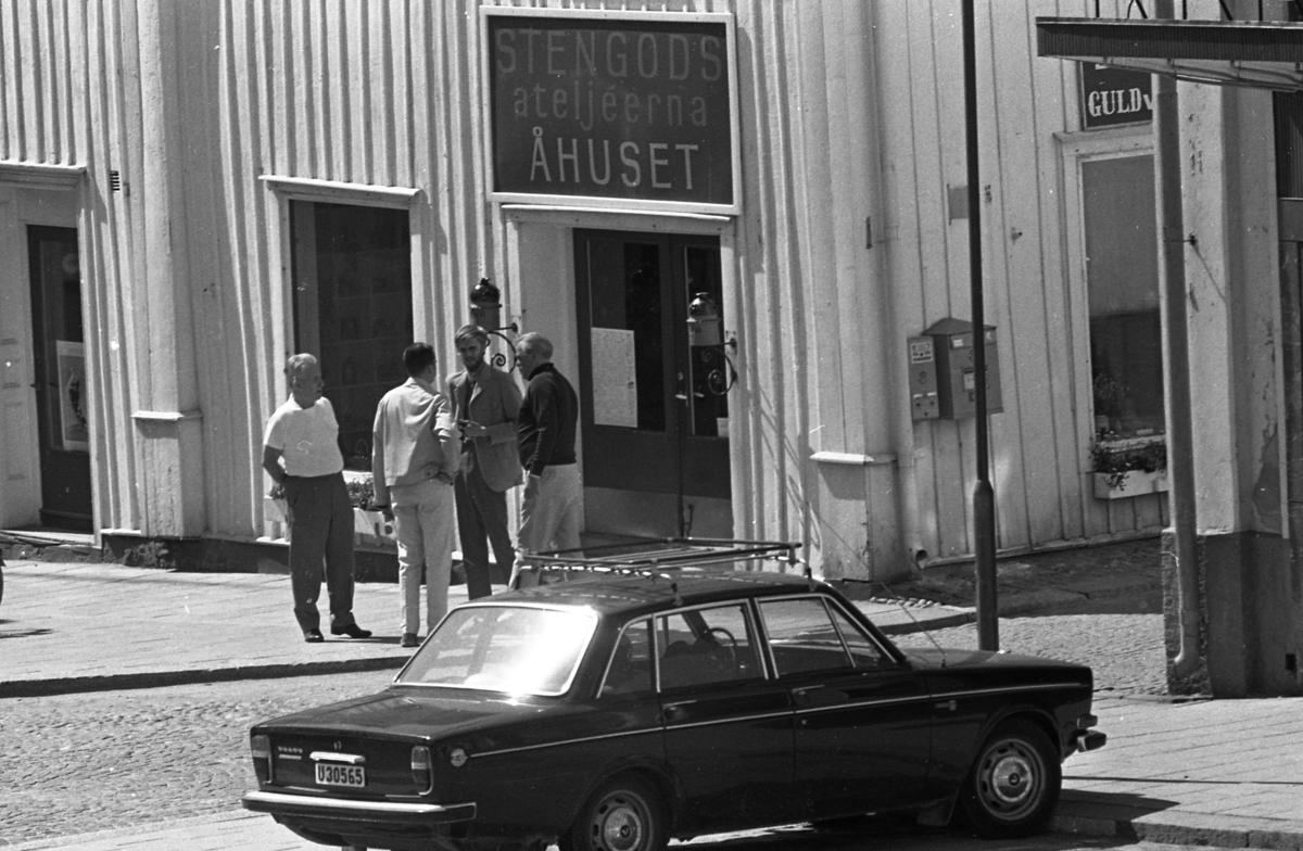 Författaren Wilhelm Moberg (till höger) besöker Arboga. Han samtalar med tre herrar utanför ateljé Åhuset vid Stora torget. Mannen med ryggen mot butiken kan vara Jan Wilhelmsson. En brevlåda hänger på väggen mot Västerlånggatan. En Volvo står parkerad i förgrunden.