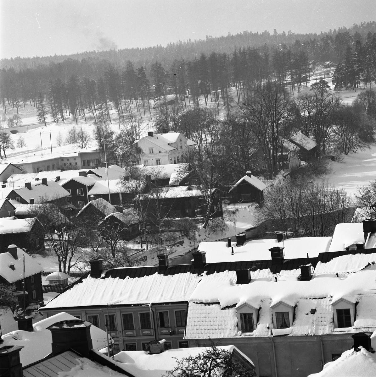 Närmast, i bild, ligger kvarteret Kungsgården och där bortom kvarteret Stadsgården. Fastigheter vid Storgatan. Byggnader vid Vinbäcken anas längst bort i bilden. Vy över Arboga centrum och västerut. Utsikt.