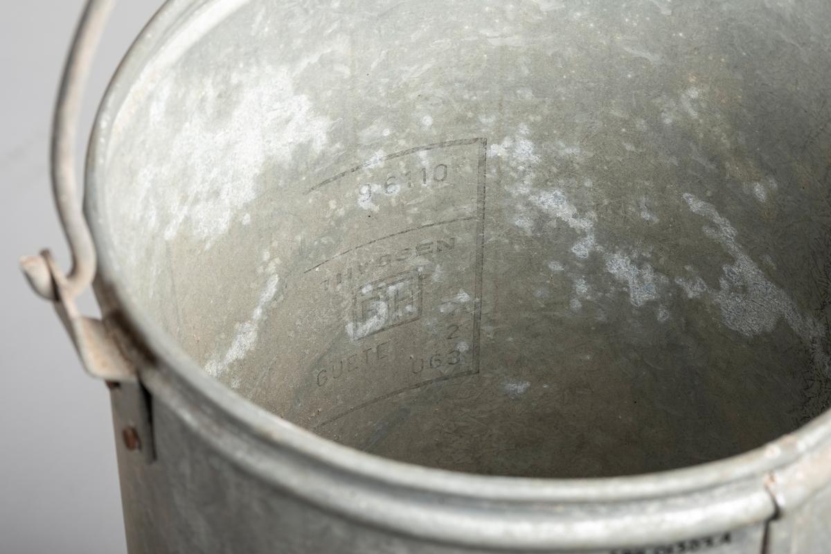 Sylinderformet beholder som står på tre ben i et rundt kar. Beholderen har åpning i bunn. Det er håndtak på beholderen som går over lokket.