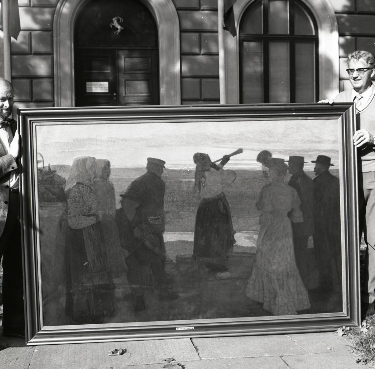 """Två män håller upp tavlan """"På blacksås"""" målad av John Sten. Framför entrén till Hälsinglands museum, 1974-1975."""