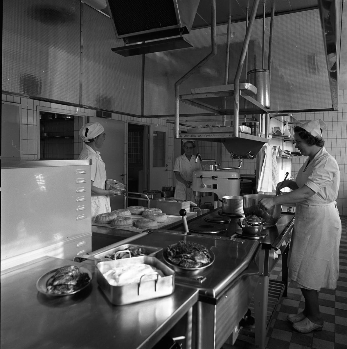 Interiör från köket på det nya ålderdomshemmet, Strömsborg. Tre kvinnor i arbete. Till vänster står Olga Larsson och bakar sockerkakor. Anna-Lisa Söderberg skymtar bakom hushållsmaskinen. Margit Wirzelius rör om i grytan.