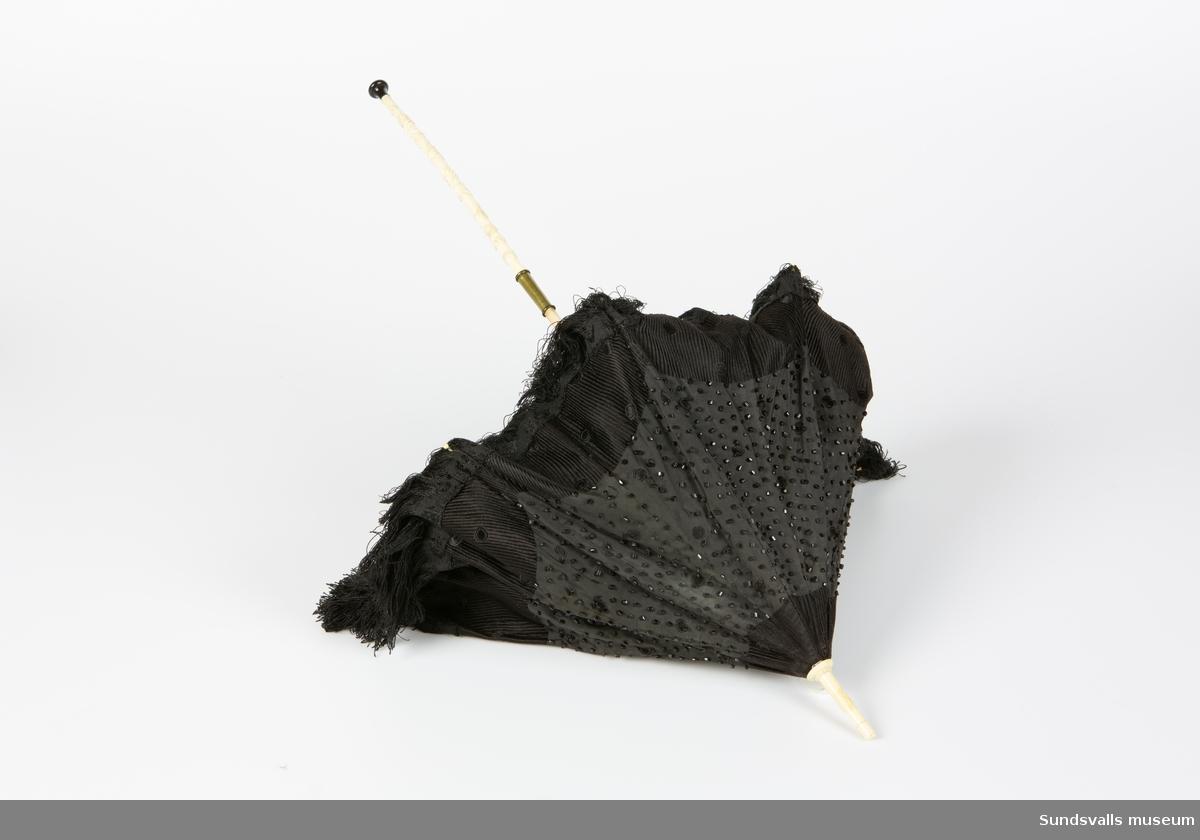 Svart parasoll med vikbart skaft i två material, trä och ev ben med skuren dekor. Svart knopp nedtill. Parasollet är broderat med svarta pärlor och försett med fransar.
