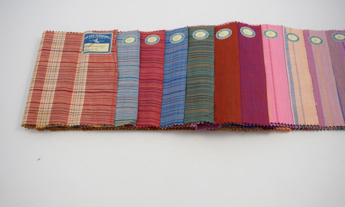 """Rektangulære, lange tekstilprøver stiftet sammen med papiromslag. Hver stoffprøve er merket med en klistrelapp med nummer. Heftet viser kvalitet """"Bordestof"""" og design 57, 44, 54, 45, 50, 40, 41, 12, 8, 10, 13, 9, 3, 5, 6, 7, samt kvalitet """"Bordestoff F"""" og design 4, 5, 6,"""