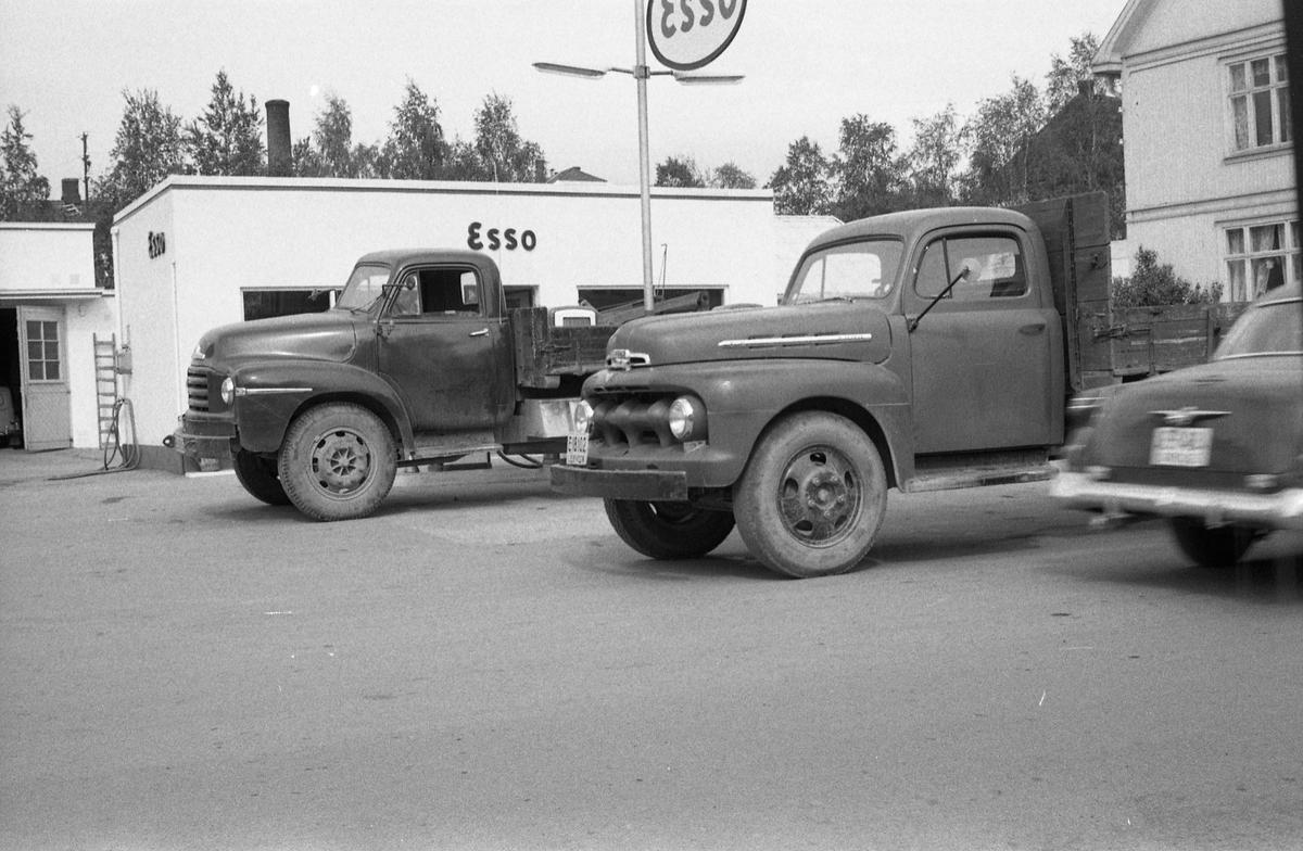 Gatebilde fra Lena. I bakgrunnen Esso bensinstasjon. En lastebil står parkert ved bensinpumpene, en annen i gatekanten, mens en personbil er i fart ut av bildet og i motsatt retning.. Mai 1959.